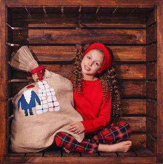 Piękne słodkie dziewczyny dziecko w drewnianej kwadratowej lokalizacji w ozdób choinkowych