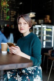 Piękne słodkie dziewczyny w kawiarni, patrząc na kamery z kawą uśmiechający się. zielony sweter z dzianiny. modnie ubrana dziewczyna. dziewczyna patrzy na telefon. dama biznesu