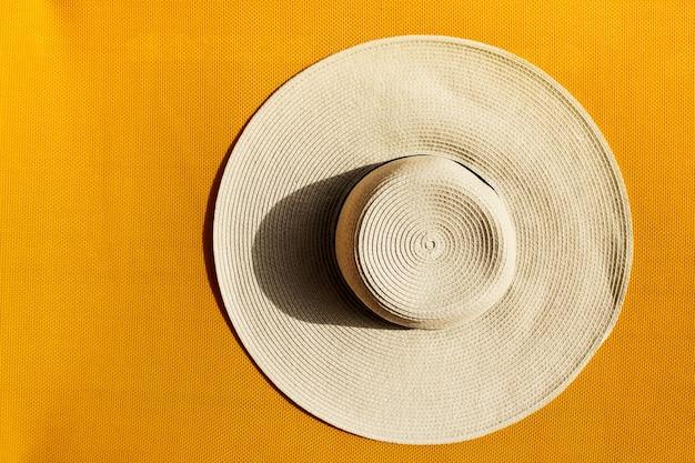 Piękne słomianego kapelusza na żółtym tętniącego życiem żywy tła. widok z góry.