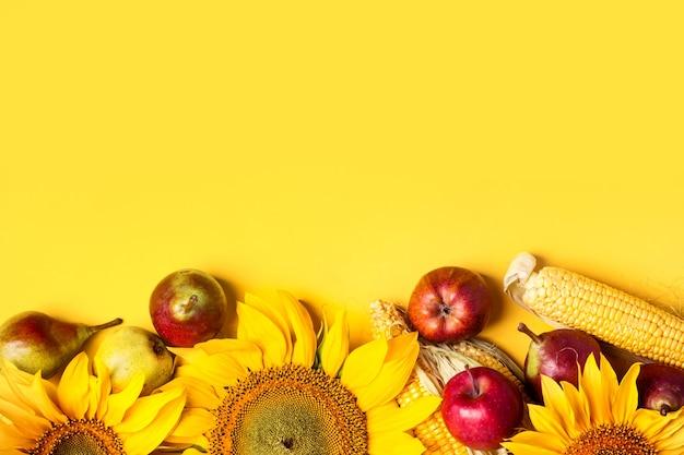 Piękne słoneczniki, gruszki i kukurydza na żółtym tle. koncepcja zbiorów wakacje.