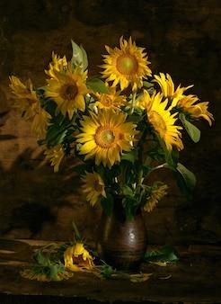 Piękne słoneczniki w wazonie na drewnianym tle