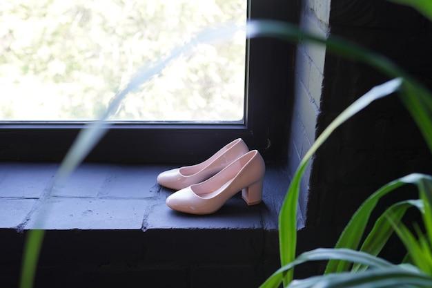 Piękne ślubne złote szpilki. buty ślubne luksusowego projektanta na ciemnym oknie.