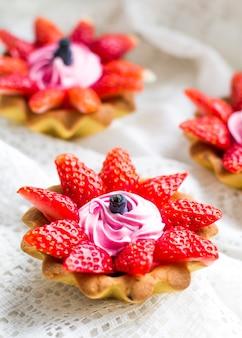 Piękne smaczne babeczki z truskawkami, wiciokrzewem i różową śmietaną