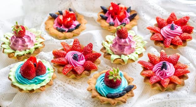 Piękne smaczne babeczki z truskawkami, wiciokrzewem, kremem niebieskim i różowym