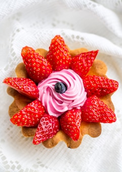 Piękne smaczne ciastko z bliska z truskawkami, wiciokrzewem i różową śmietaną