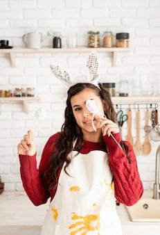 Piękne śmieszne brunetka kobieta w czerwonym swetrze i białym fartuchu ubrana w uszy królika, zasłaniając oczy dekoracjami pisanek