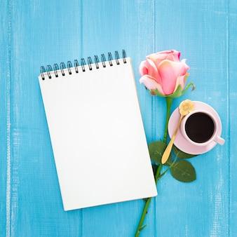 Piękne śniadanie z różami i filiżanką kawy na niebieskim drewnianym