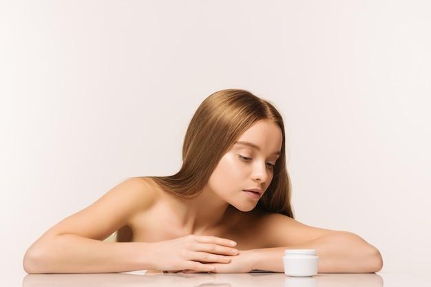Piękne spa dziewczyna z słoik kremu na białym tle - obraz