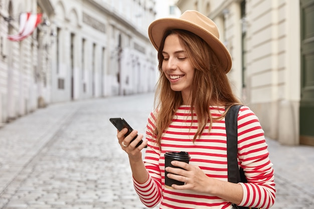 Piękne spacery turystyczne ulicami miasta, używa nawigatora online do znalezienia właściwej drogi, trzyma telefon komórkowy