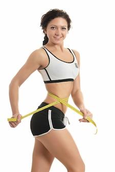 Piękne sportowe ciało kobiety z żółtą miarą