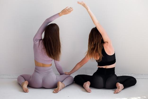 Piękne sportowe kobiety wykonują ćwiczenia na białym tle fitness wysokiej jakości zdjęcie