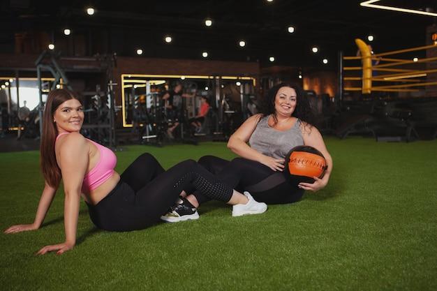 Piękne sportsmenki plus size, które wspólnie ćwiczą na siłowni