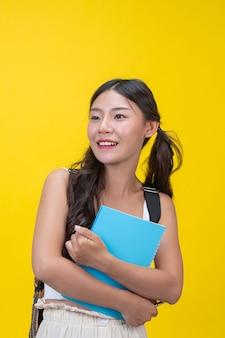 Piękne studentki posiadają zeszyty i długopisy