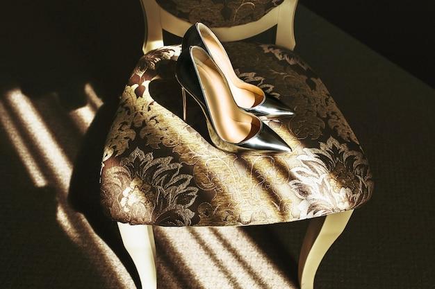 Piękne stylowe eleganckie srebrne buty ślubne na krześle