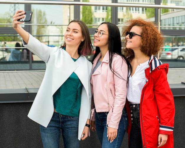 Piękne stylowe koleżanki biorąc selfie w smartfonie