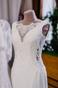 Piękne suknie ślubne, suknia ślubna wisząca na wieszakach i manekiny w studio