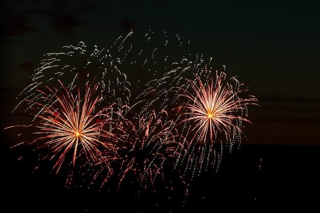 Piękne świąteczne fajerwerki na nocnym niebie jasny, wielokolorowy salut na czarnym tle