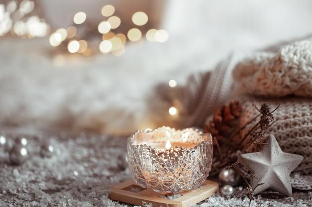 Piękne świąteczne świeczki w świeczniku na jasnym tle zamazane pole. pojęcie domowego komfortu i ciepła.