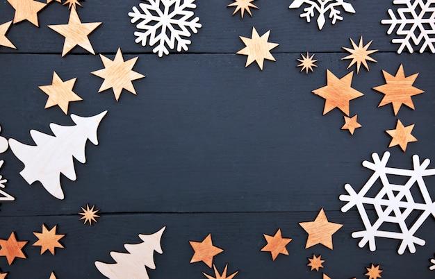 Piękne świąteczne tło z dużą ilością małych drewnianych ozdób na ciemnym drewnianym biurku.