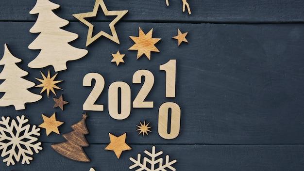 Piękne świąteczne tło z wieloma małymi drewnianymi dekoracjami i drewnianymi numerami 2021 na drewnianym biurku.