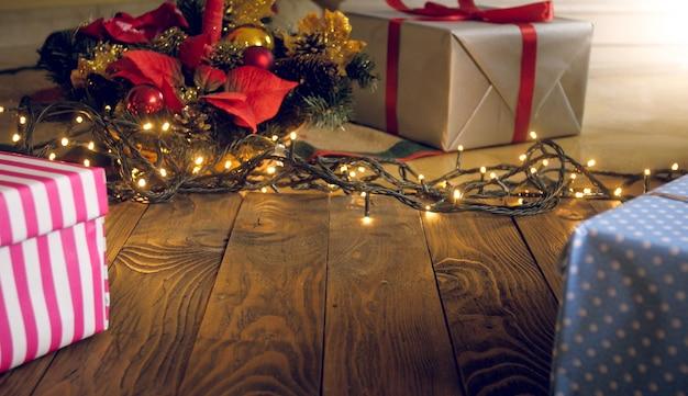 Piękne świąteczne tło ze światłami, prezentami i choinką na drewnianej flory. skopiuj miejsce na tekst lub projekt
