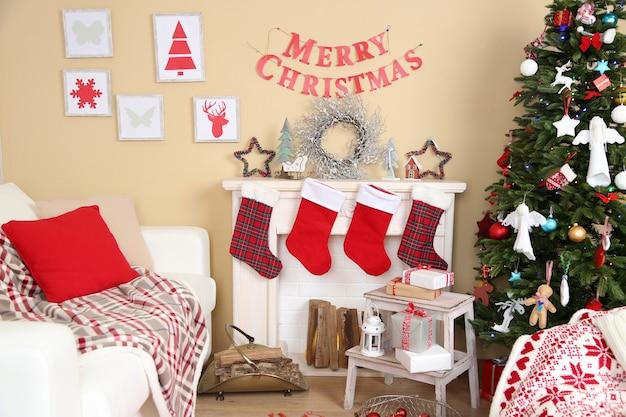 Piękne świąteczne wnętrze z sofą, ozdobnym kominkiem i jodłą