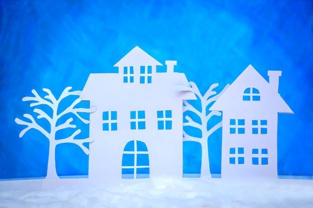 Piękne świąteczne zdjęcie przedstawiające wycięte z papieru domy i zimowe drzewa na niebieskim tle