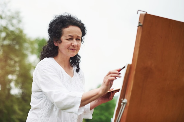 Piękne światło słoneczne. portret dojrzały malarz z czarnymi kręconymi włosami w parku na świeżym powietrzu