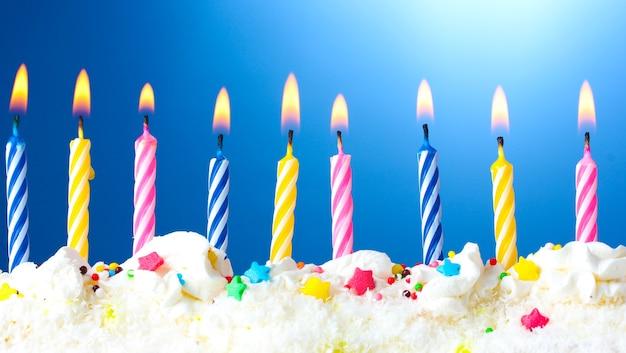 Piękne świeczki urodzinowe na niebieskim tle