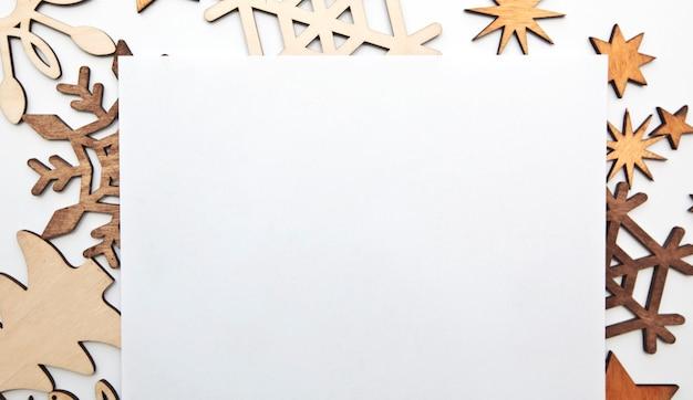 Piękne święta z mnóstwem małych drewnianych ozdób na białym biurku.
