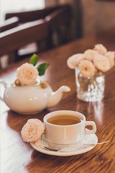 Piękne świeże róże przy filiżance herbaty i romantyczny nastrój w pastelowych odcieniach.