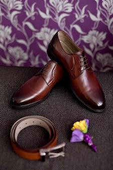 Piękne szczegóły ślubu z ceremonii i przyjęcia. męskie buty, pasek. brązowy.