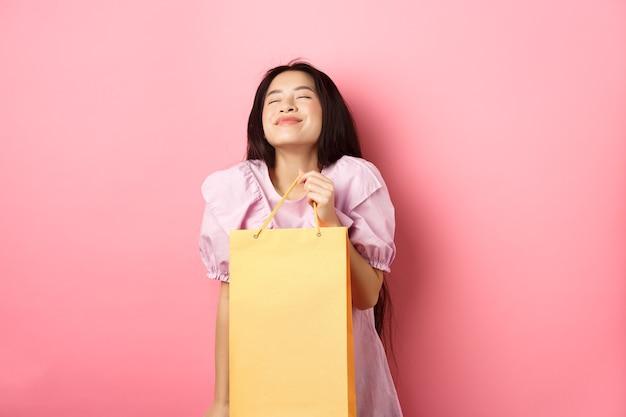 Piękne szczęśliwe azjatyckie kobiety trzymającej torbę na zakupy, uśmiechając się z zamkniętymi oczami, stojąc w sukience na różowym tle.