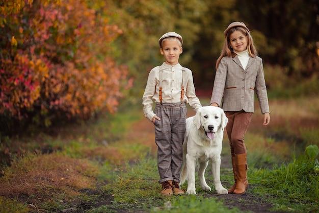 Piękne, szczęśliwe dzieci, brat i siostra, spacerują ze swoim psem
