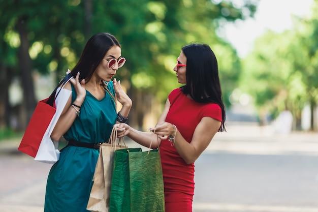 Piękne szczęśliwe kobiety patrzeje w torba na zakupy chodzi przy ulicą w słońc szkłach