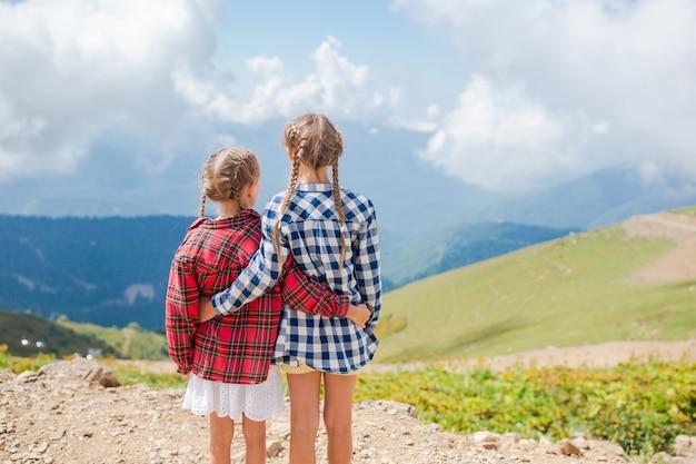 Piękne szczęśliwe małe dziewczynki w górach w scenie mgła