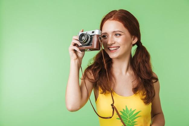 Piękne szczęśliwe młode rude dziewczyny fotograf pozowanie na białym tle na tle zielonej ściany trzymając aparat.
