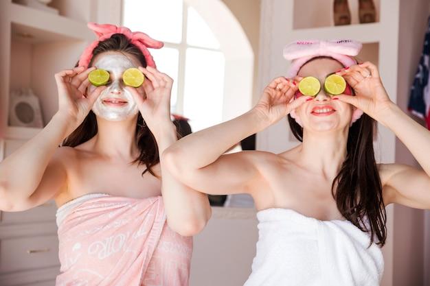 Piękne, szczęśliwe, pozytywne kobiety owinięte w ręcznik, kosmetyczny bandaż na głowie i z limonkami na oczach. dziewczyny uśmiechają się i patrzą w kamerę.