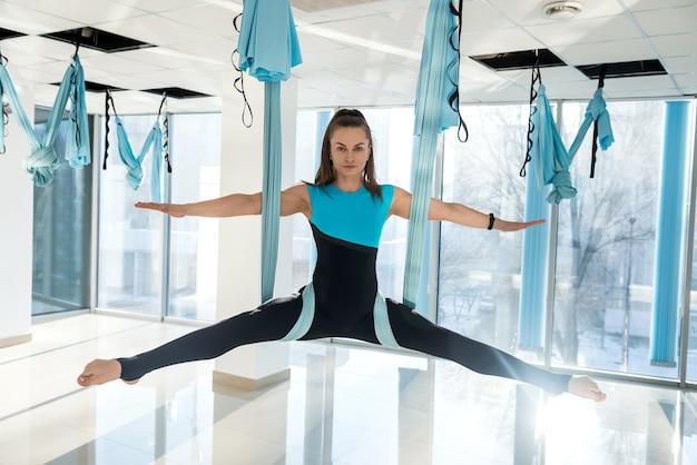 Piękne, szczupłe ciało dziewczyna praktykuje jogę mucha na siłowni. lataj sportem jogi