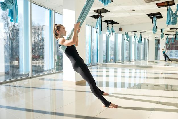 Piękne, szczupłe ciało kobiety praktykujących jogę latania na siłowni