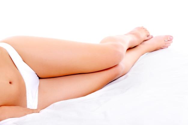 Piękne, szczupłe, gładkie nogi leżącej kobiety na białym łóżku