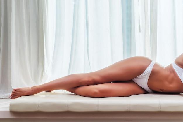 Piękne, szczupłe nogi kobiece na sobie białą bieliznę, leżąc na łóżku z jasnym oknem i zasłonami