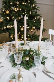 Piękne szklane kieliszki, świece w wystroju świątecznego stołu.