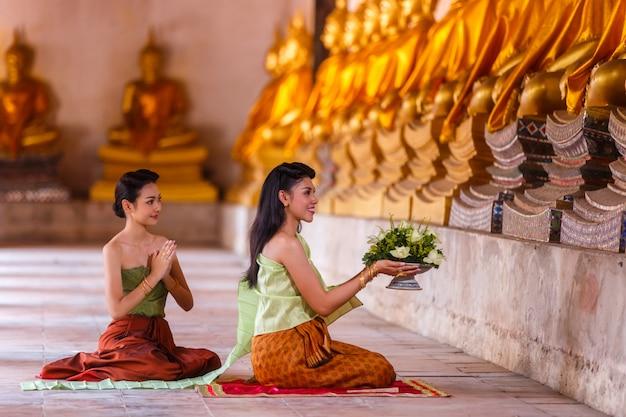 Piękne tajlandzkie dziewczyny w tajlandzkiej tradycyjnej kostiumowej modli się buddha statui w ayutthaya