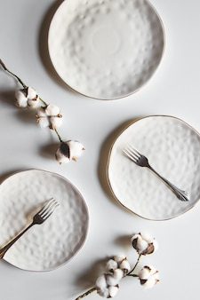 Piękne talerze na białym tle z bawełną. piękny układ