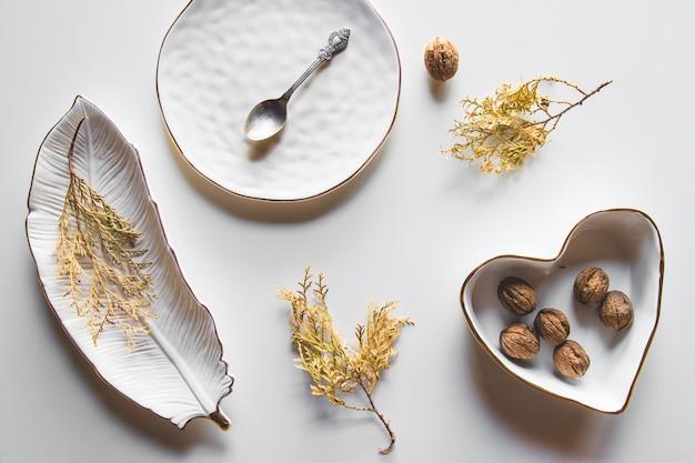 Piękne talerze na białym tle z suszoną rośliną. piękny układ