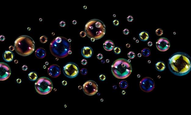Piękne tęczowe bańki mydlane unoszące się w ciemności