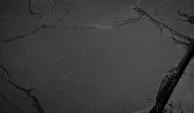 Piękne tło ciemnego kamienia łupkowego w zbliżeniu. idealny do projektu kulinarnego lub prezentacji produktu.