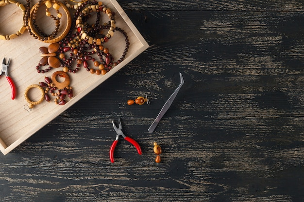Piękne tło dla warsztatów. narzędzia do tworzenia biżuterii, kolorowe kamienne koraliki i znaleziska metalowe.