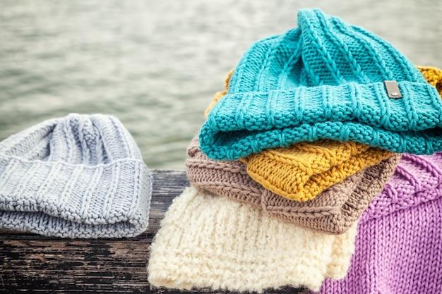 Piękne tło dziania zima niebieski i żółty kapelusz dużo. szydełko wykonane ręcznie. zbliżenie czapek z dzianiny w kolorze niebieskim, żółtym, różowym i białym